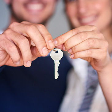 Photo of couple holding key representing mortgage